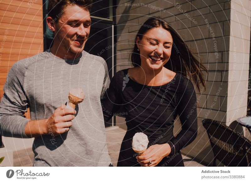 Cheerful relaxed couple laughing while leaving cafe and eating ice cream in summer sunny day cheerful street relationship date hug fun dessert cone positive