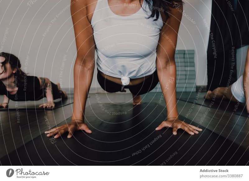 Woman practicing yoga in flying pigeon position woman practice pose body barefoot training one legged plank class fitness studio stretch healthy physical