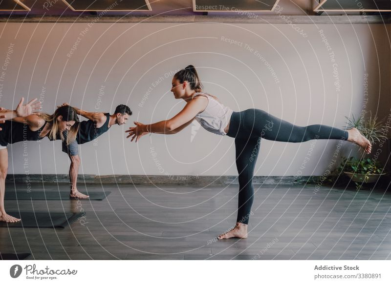 Adult people practicing yoga together in balance pose and stretching body in light contemporary studio warrior pose instructor exercise practice class lesson