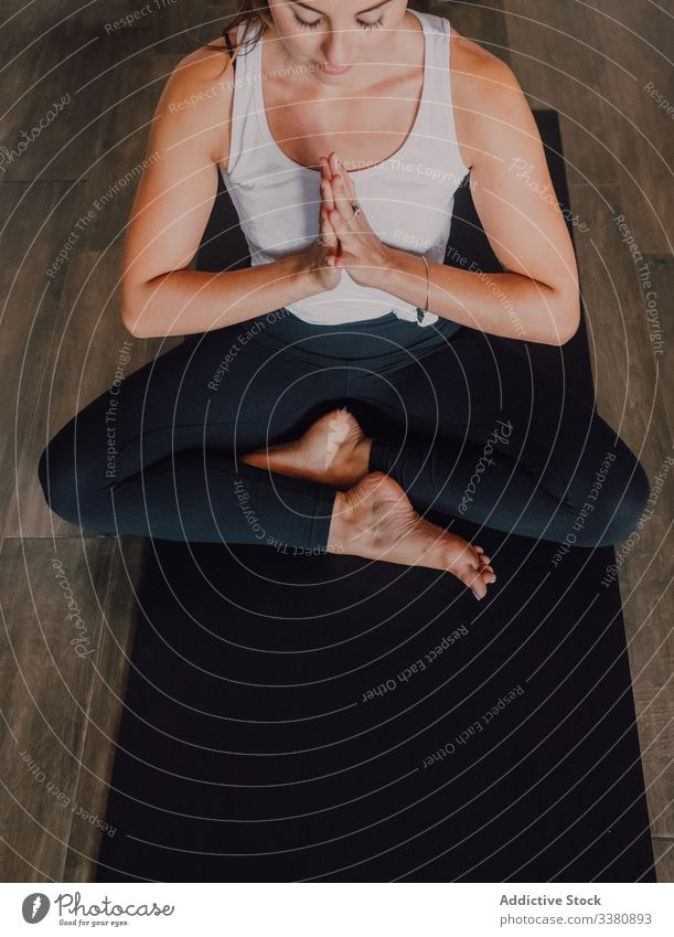 Slim barefoot woman meditating in bound angle pose in contemporary workout room meditation yoga relax practice asana namaste exercise training athletic stretch