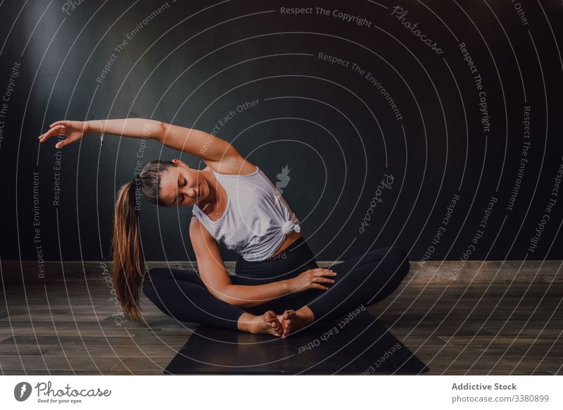 Slender barefooted woman stretching body in bound angle pose in contemporary studio yoga practice exercise training athletic workout position spirituality