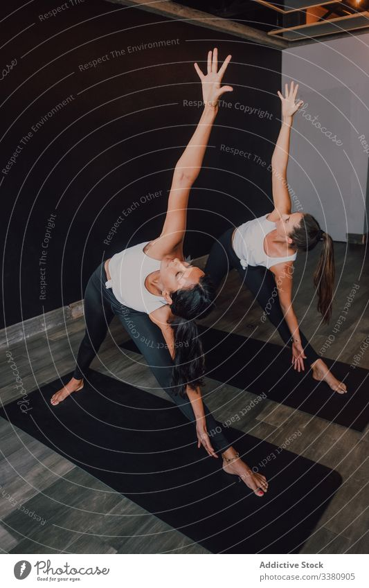 Women stretching body practicing yoga in revolved triangle pose exercise practice balance mat class lesson training parivrtta trikona together asana motivation