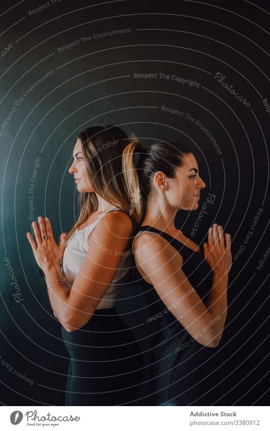 Fit adult women in mountain pose with namaste in dark room relax yoga calm meditate figure training athlete fit tranquil beauty together tadasana exercise