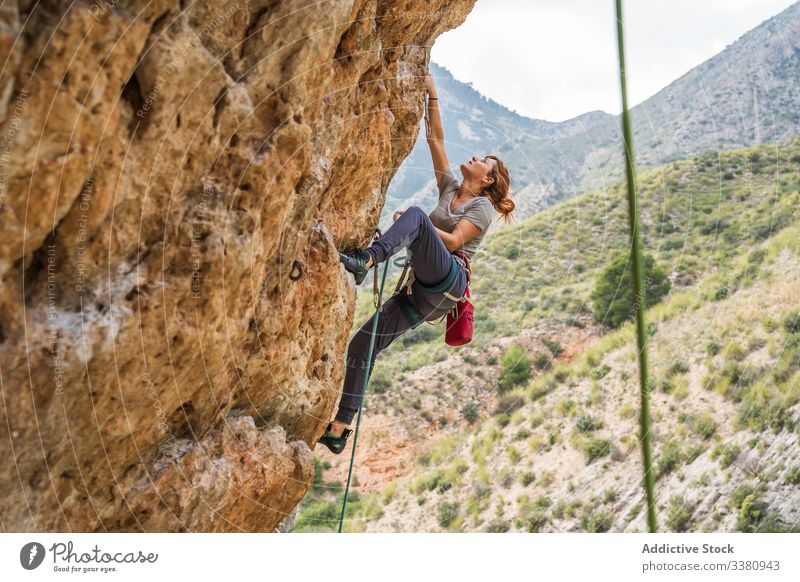 Active female climber ascending on cliff woman alpinist mountain practice climbing active mountaineering risk travel brave adventure courage altitude extreme