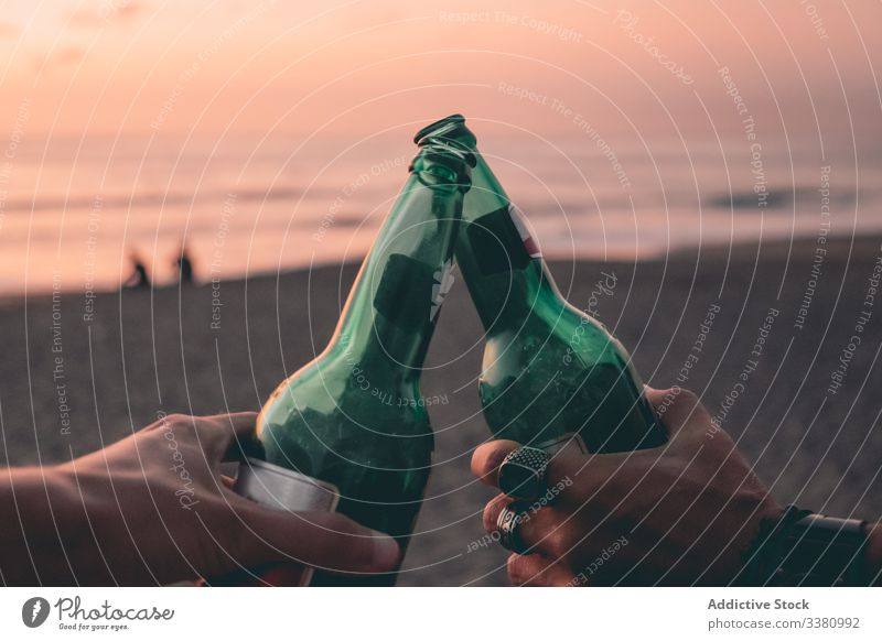 Friends toasting with beer on sunset beach bottle friend summer sea sky hand clink together relax enjoy drink alcohol beverage weekend evening vacation coast