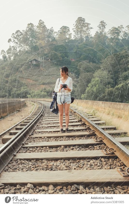 Female tourist walking on lonely railway against exotic forest woman take photo camera empty photography green bridge plant tourism travel nature lifestyle