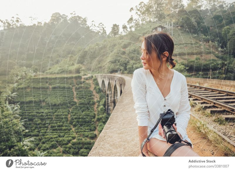 Young Asian woman on vacation taking photo with camera in nature tale photo travel exotic jungle railroad explore view tourism photography sit fence green plant