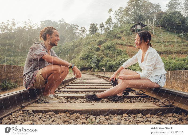 Woman shooting man with camera while sitting on railroad couple travel take photo tropical exotic together explore memory tourism rails freedom cheerful relax