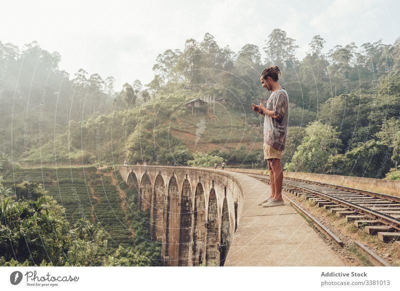 Man on vacation browsing smartphone on bridge man tourism travel watching take photo landscape tropical using mobile phone sri lanka asia green plant exotic