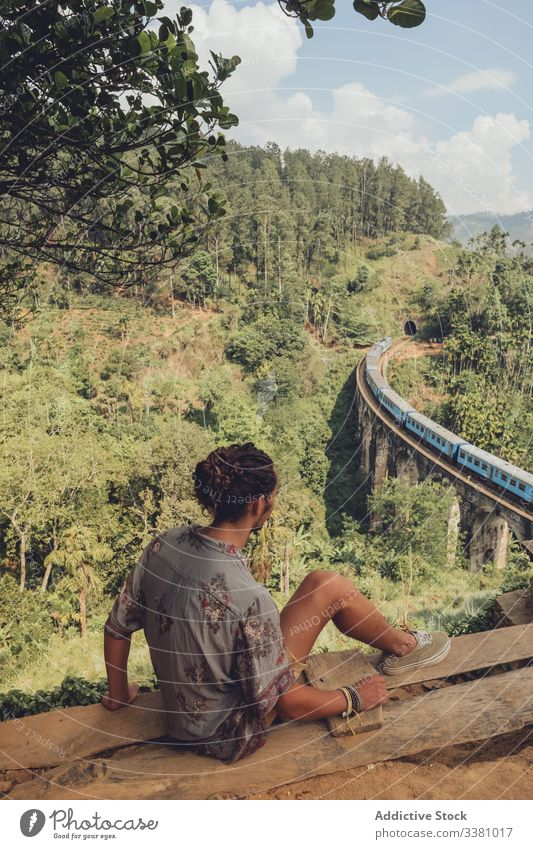 Anonymous man on vacation enjoying view from peak of hill viewpoint tourism bridge landscape tropical travel train railroad trip green tree plant nature journey