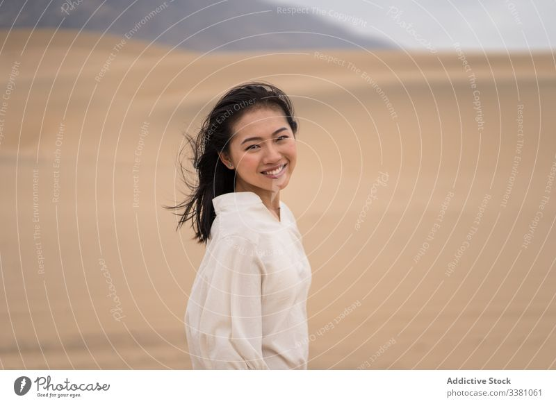Cheerful young ethnic female tourist enjoying vacation in desert woman sandy explore tourism travel nature adventure dry traveler beauty freedom happy journey