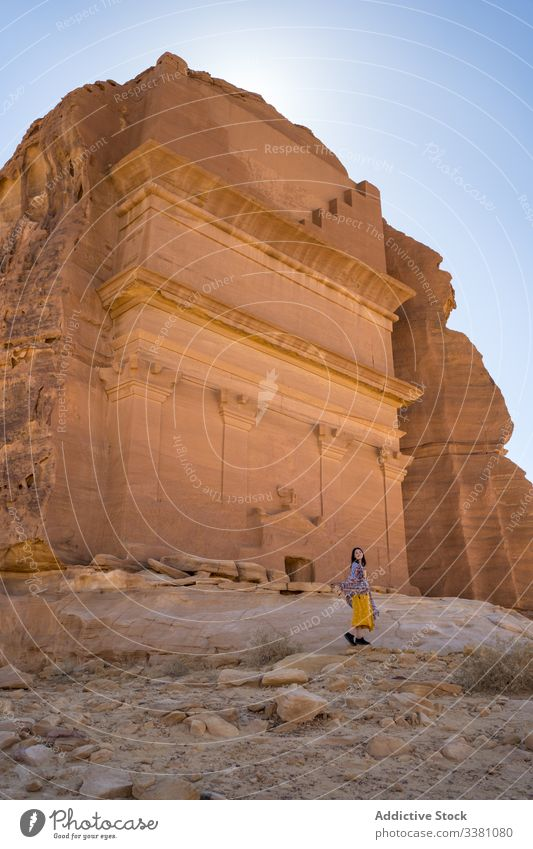 Excited female tourist enjoying sightseeing in desert woman tomb carved cliff traveler freedom vacation tourism culture grave religion architecture old location