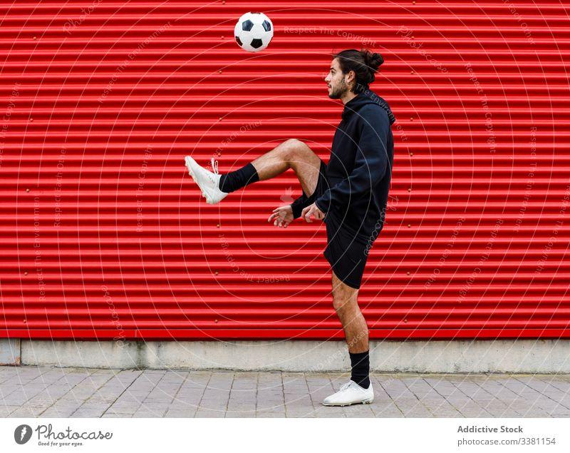 Man playing soccer ball on street man training feint kick football sport activity game male energy urban motion healthy lifestyle guy sportsman summer