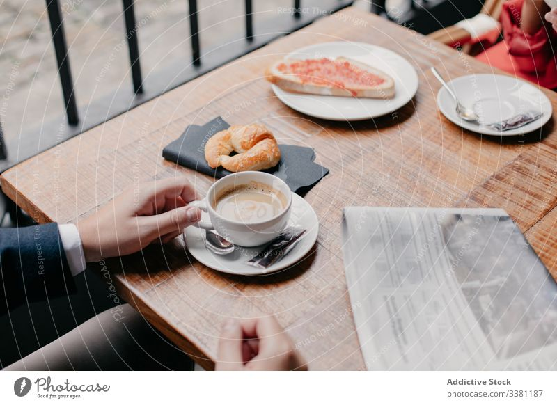 Couple drinking coffee in cafe couple breakfast together romantic table cup newspaper morning relax rest cafeteria casual meeting relationship lifestyle