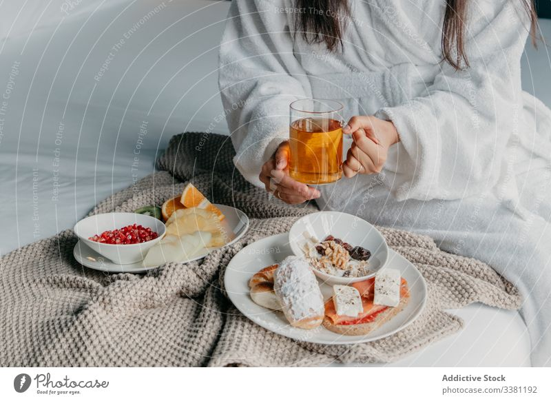 Anonymous woman having breakfast in bed tea happy bathrobe cheerful mug cup drink female food cozy tasty home relax fresh beverage morning delicious rest