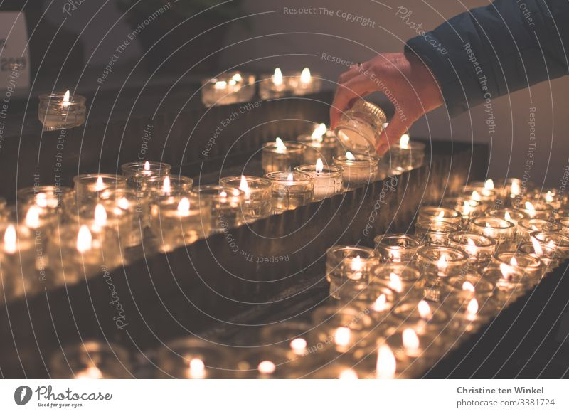 Woman lighting a candle at a candle altar Human being Feminine Adults Hand 1 30 - 45 years 45 - 60 years shoulder stand Candlelight Candlelit ambience