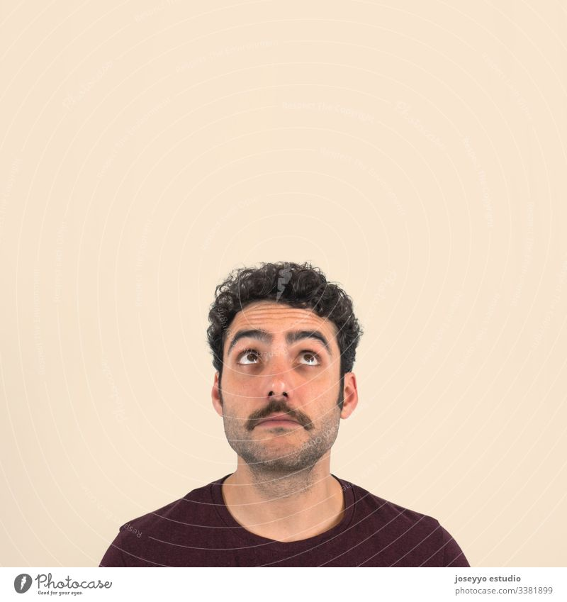 Funny portrait of a young boy with a mustache with doubtful and bewilderment  face  looking up. Purple t-shirt and isolated ochre background. 30-40 years