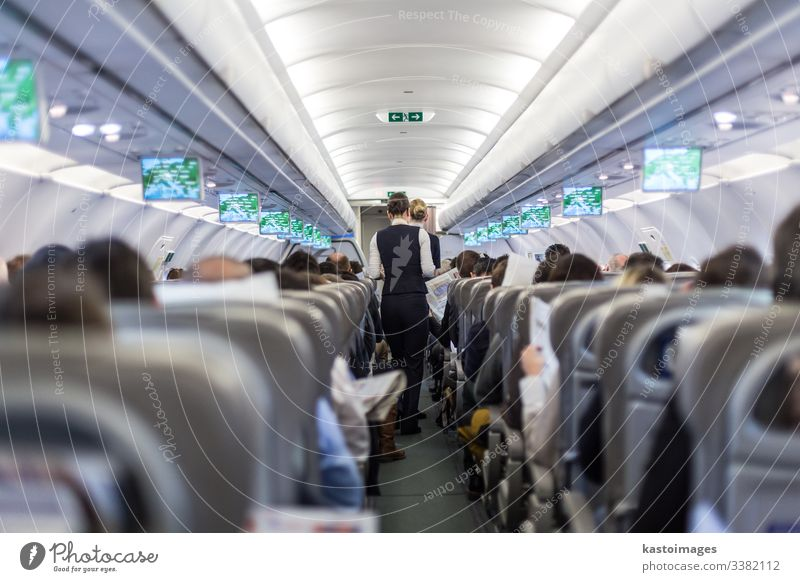 Interior of commercial airplane with stewardess serving passengers on seats during flight. flight attandant aeroplane aircraft interior cabin crowded transport