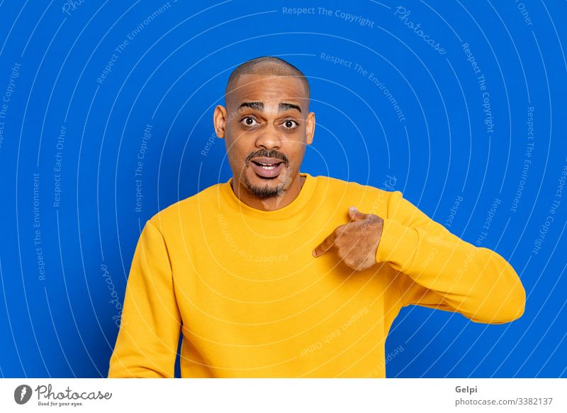 African guy with a yellow jersey black blue point indicate myself me select indicating finger selection advertisement copy space hand sign choose adult people