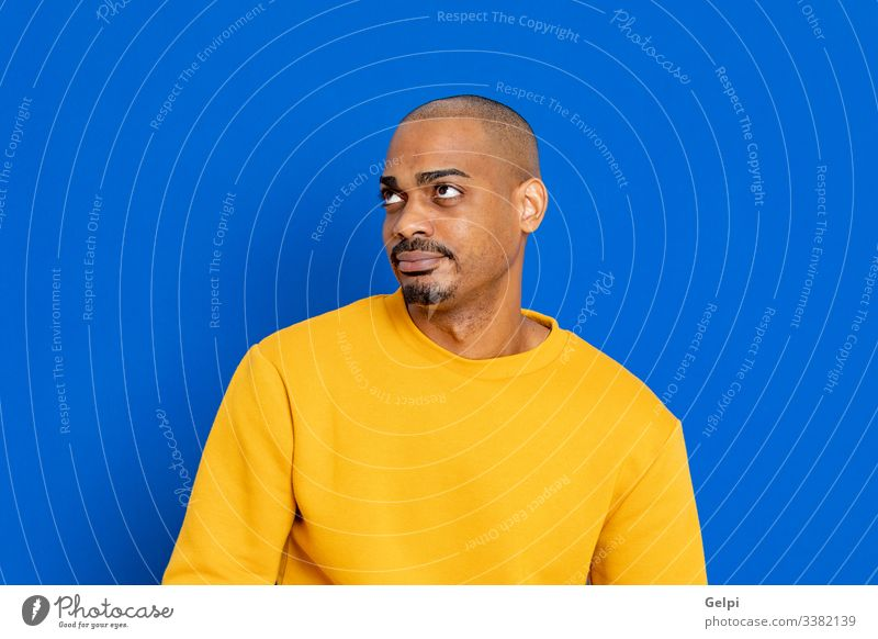 African guy with a yellow jersey black blue red happy smile joyful positive relaxed looking adult people person african male american man isolated background