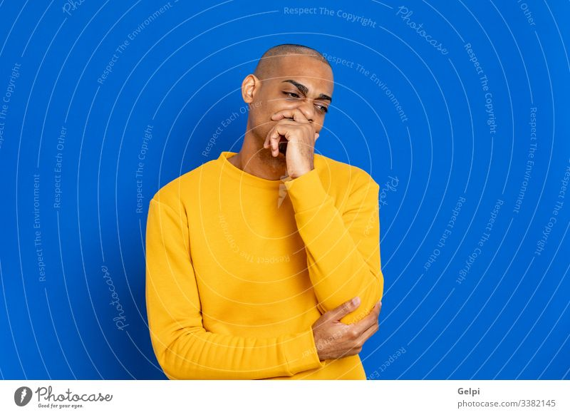 African guy with a yellow jersey black blue pensive think imagine imagination idea solution doubt doubtful thinking smart clueless balance adult people person