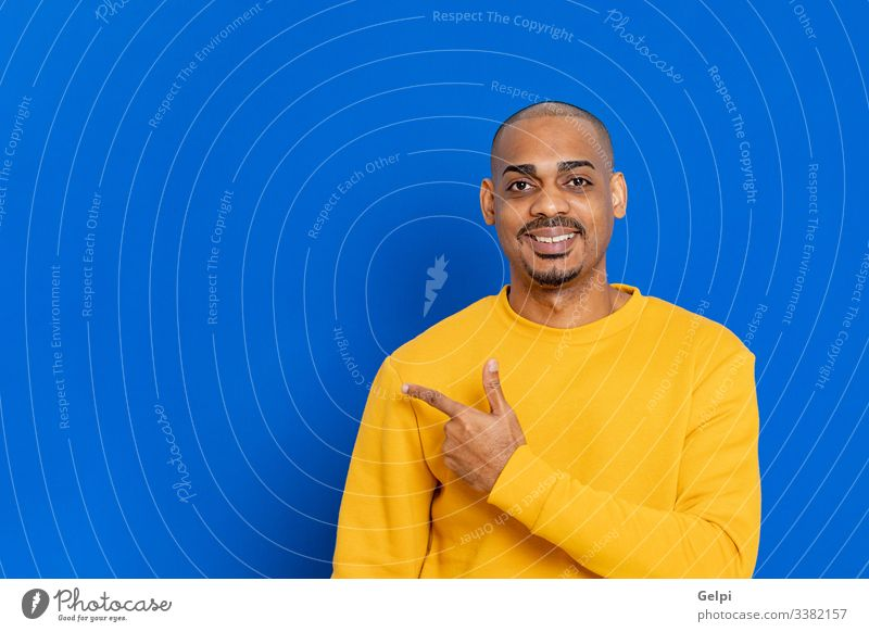 African guy with a yellow jersey black blue point indicate indicating finger advertisement adult people person african male american man isolated background