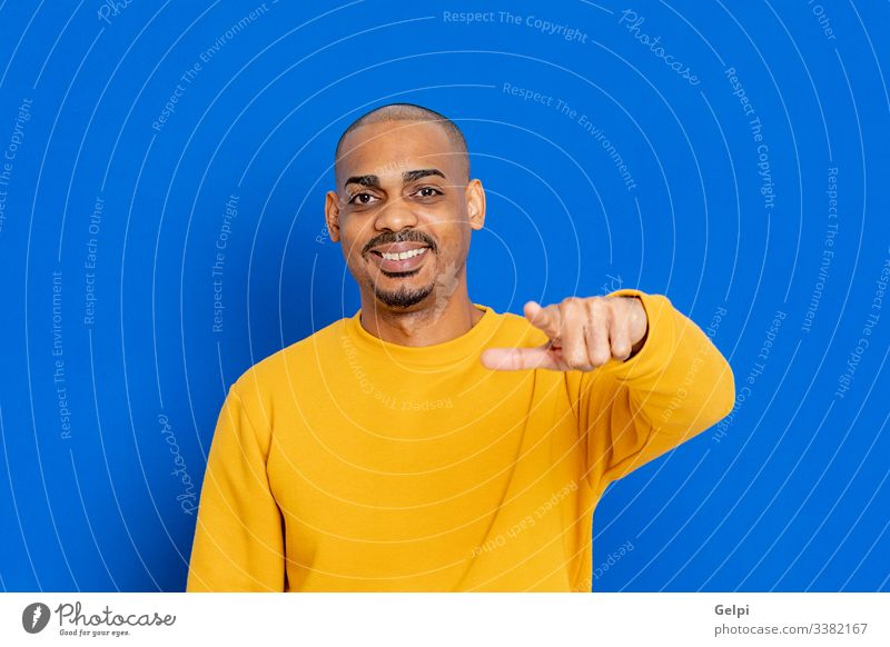 African guy with a yellow jersey black blue hand you pointing accuse laugh indicate selecting selection finger adult people person african male american man