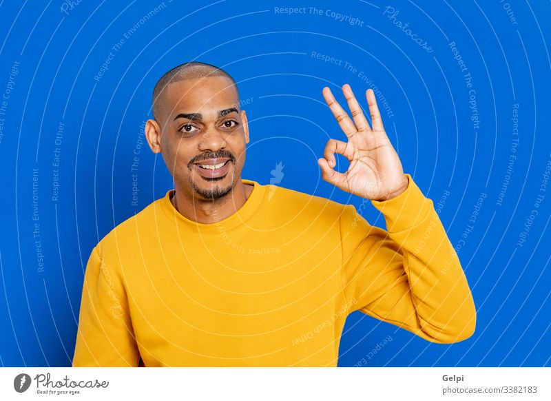 African guy with a yellow jersey black blue Ok accept yes happy smile funny sigh finger hand adult people person african male american man isolated background