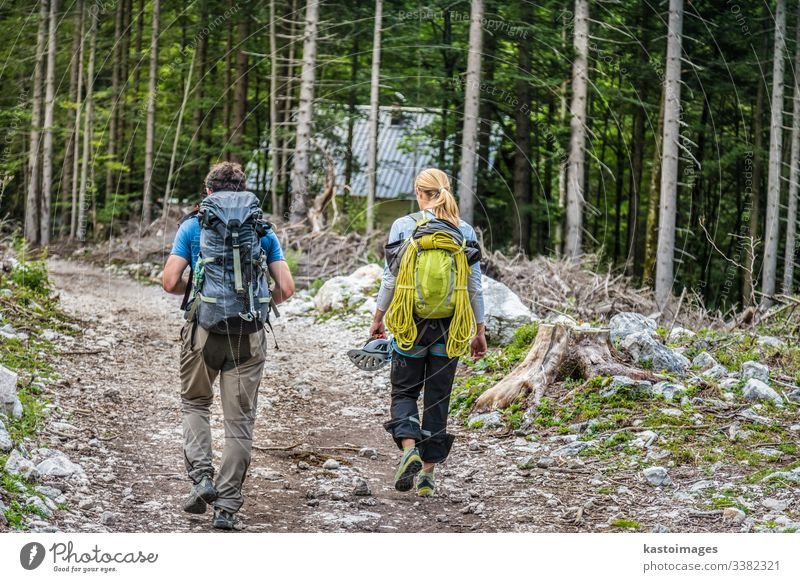 Rear view of two young active couple walking down the trail path on forest. adventure hike hiking nature lifestyle backpack people travel trekking girl mountain