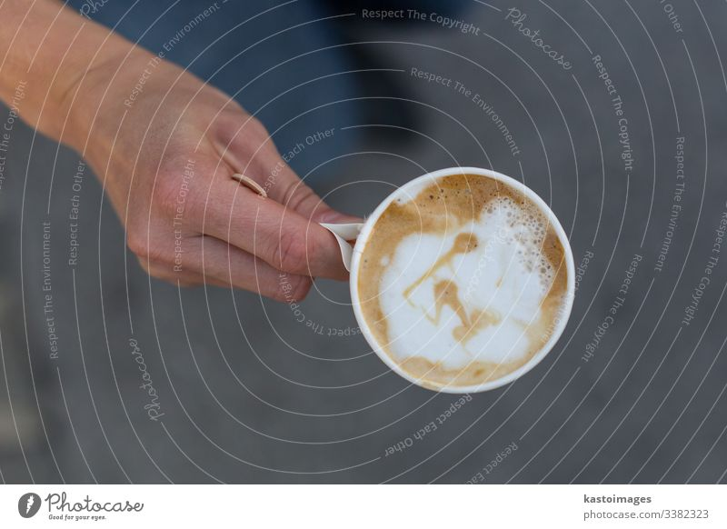 Hand holding a cup of coffee to go. latte paper art take away top view plastic drink disposable cappuccino cafe white work black break breakfast caffeine city