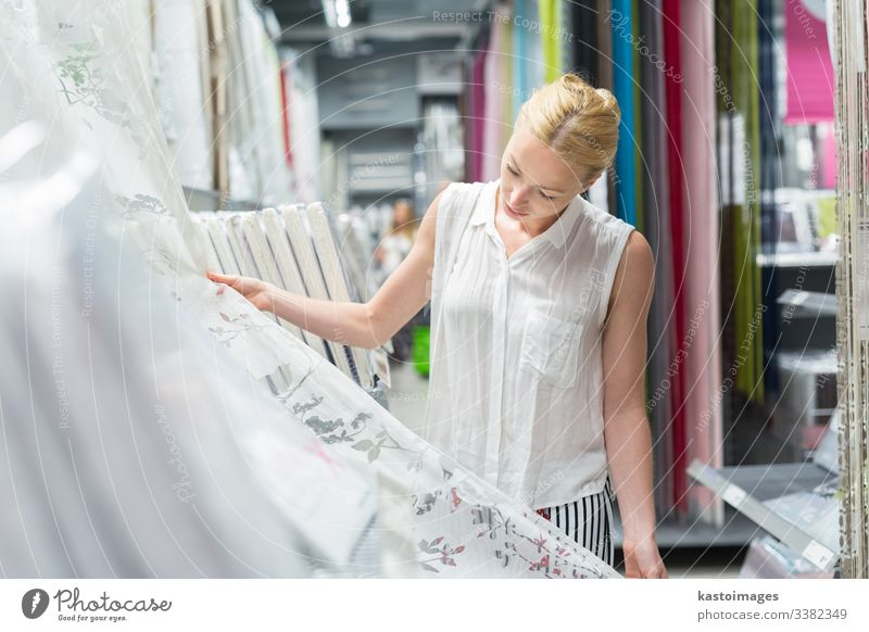 Beautiful housewife buying white curtains in home decor furnishings store. shop woman textiles beautiful retail buyer choice sale choose design female girl