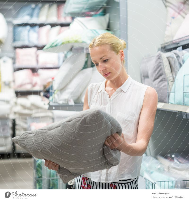 Pretty, young woman choosing decorative pillow for her sofa in a modern home furnishings store. shop buy bedding mattress furniture choose adult blankets check