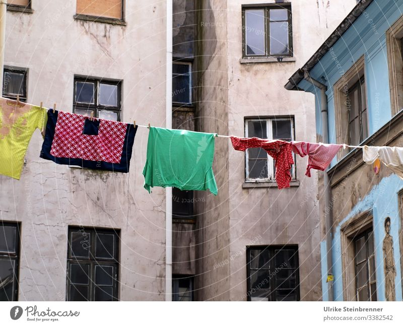 Coloured laundry on a line in the backyard of the Gängeviertel in Hamburg Laundry clothesline Dry corridor district Backyard Old building Gloomy colored