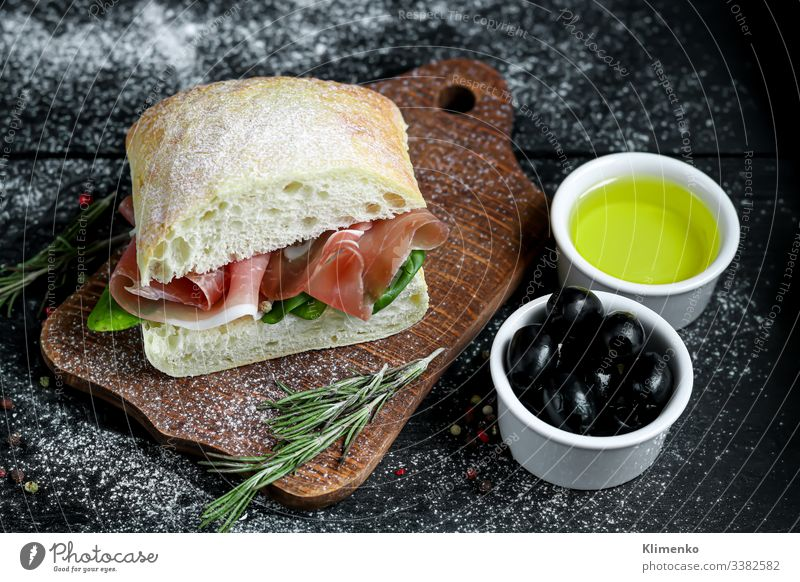 Ciabatta sandwich with arugula salad, spinach leaves, bacon. ciabatta olives rosemary oil olive oil italy bruschetta food flour breading crust snack drink