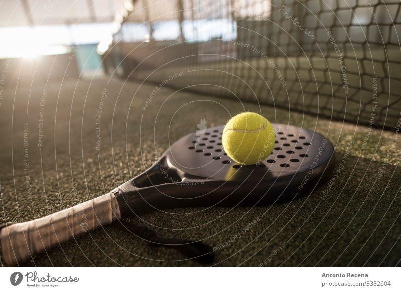 Paddle tennis racket and ball in sunset image padel paddle tennis sport paddle-tennis pádel court net tennis ball outdoors objects no people nobody fences turf