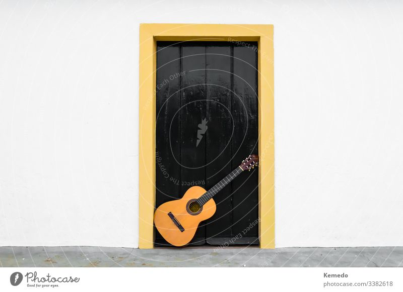 Spanish or classical guitar resting on a door of an andalusian patio. Outdoor scene of a musical instrument in the white wall of a rural house. flamenco spanish