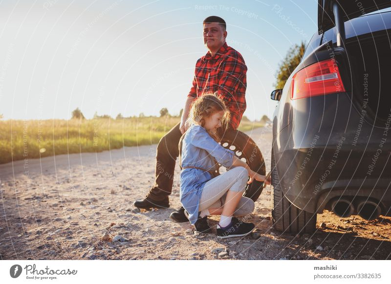 father and daughter changing broken tire during summer road trip car child family girl mechanic repair automobile man outdoors vehicle parent help dad fixing