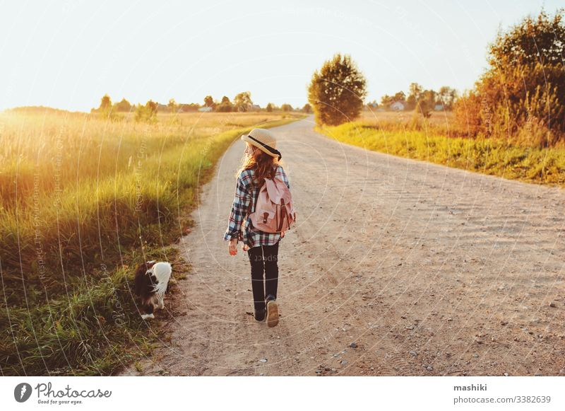 happy child girl walking country road with her dog. Enjoying summer vacations, rural living concept nature outdoor friend freedom lifestyle fun travel adventure