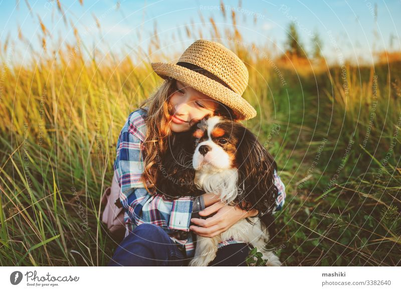happy child girl enjoying summer vacations with her dog, walking and playing on sunny meadow. Traveling, exploring new places and rural living concept nature