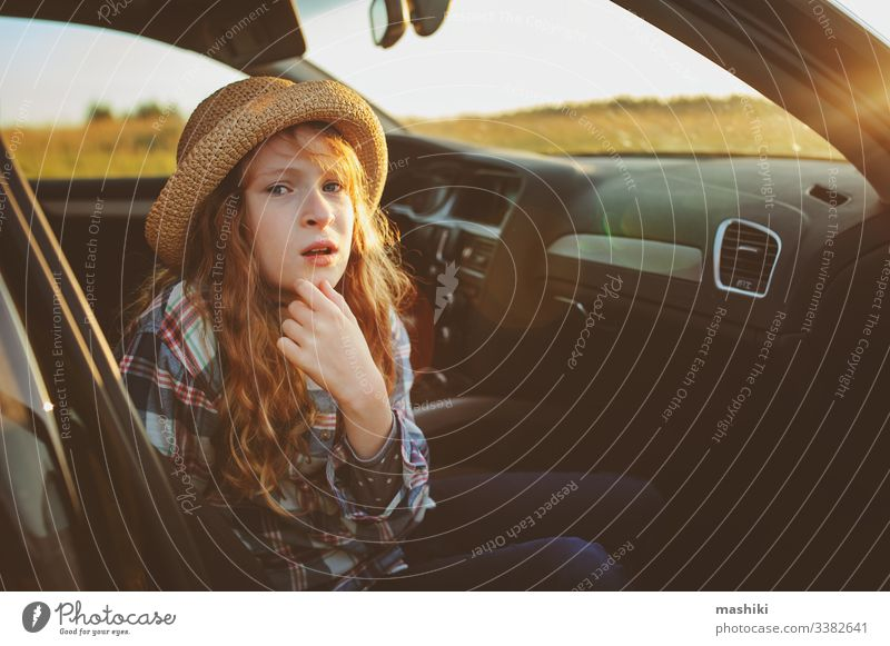 happy child girl relaxing in car during summer road trip. Exploring new places, traveling on summer vacations. nature outdoor auto drive freedom lifestyle fun