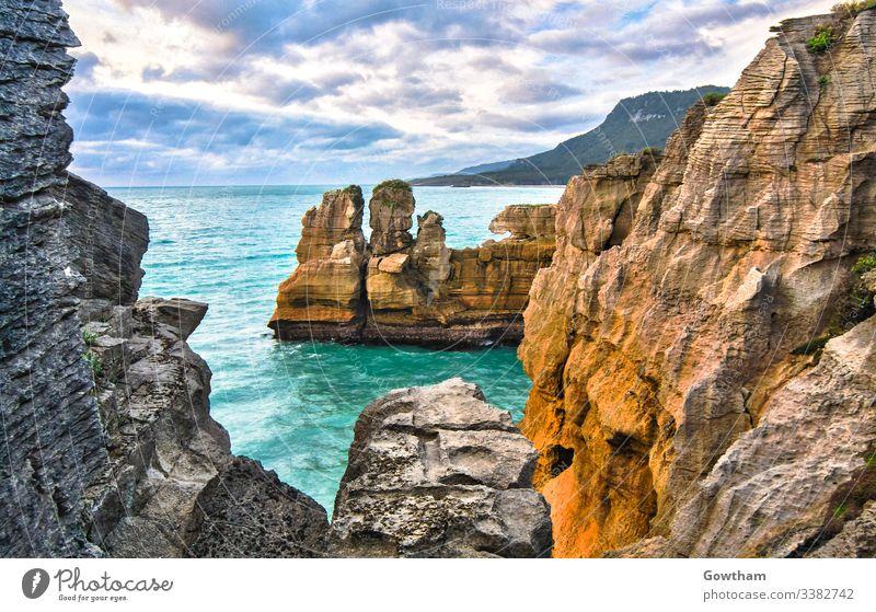 Pancake Rocks near Hokitika on New Zealand's south island. beautiful cliff cloud cloudy coast coastal color colorful colour colourful crash crashing door doors