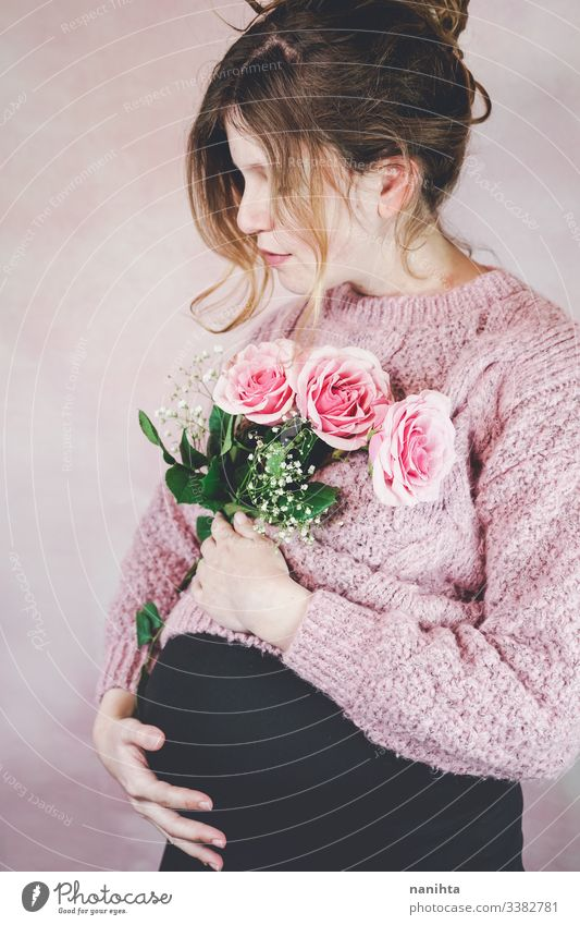 Young pregnant woman holding a bouquet of roses pregnancy mom waiting family love third trimester month weeks natural real candid real woman people flowers pink