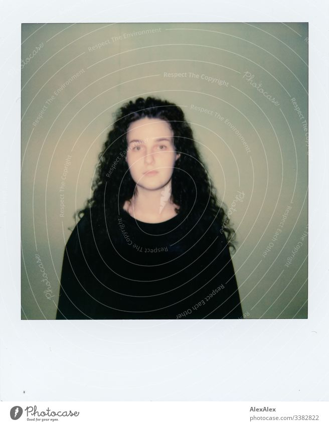 Analog Polaroid portrait of a young woman in front of a green wall Looking into the camera Portrait photograph Central perspective Shallow depth of field