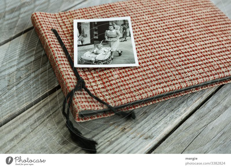 An old photo album lies on a wooden table. A photo with a mother pushing a baby carriage with a toddler. Photography Photo album Wooden table Baby carriage