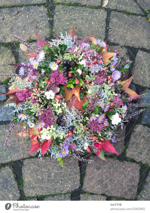 Flower wreath with fresh autumn flowers lying in bowl on paving stones Aster autumn decoration table decoration Self-made heather Sedum firecracker peas