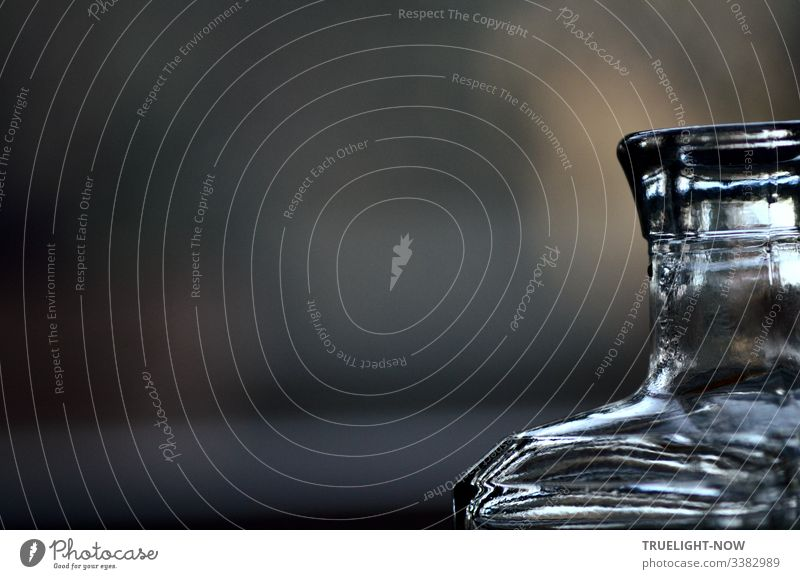 Part of an angular glass bottle focuses and reflects the morning light against a dark background Glassbottle partial view reflections somber light reflexes
