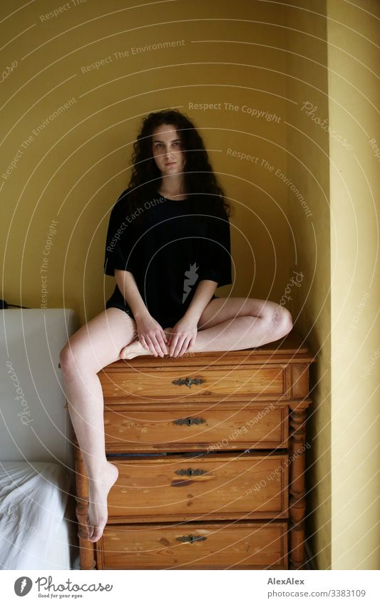 Young woman sitting on a chest of drawers in front of a yellow wall Looking into the camera Portrait photograph Central perspective Shallow depth of field Day
