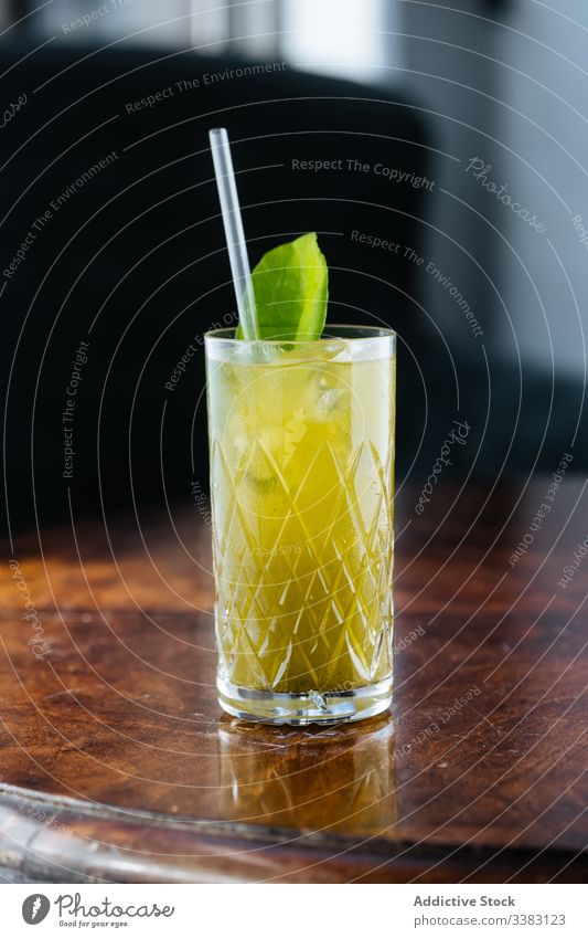 Fresh lemonade decorated with green on table glass drink mint straw beverage fruit fresh cold juice refreshment cool tasty delicious bar liquid citrus exotic