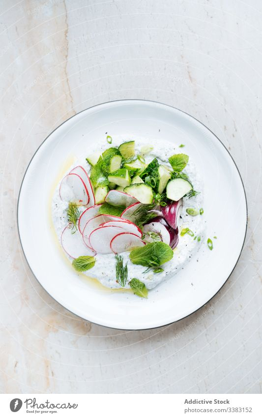 Radish salad zucchini red onion and sour cream in plate radish herb food fresh delicious tasty vegetable meal gourmet cuisine healthy nutrition diet green