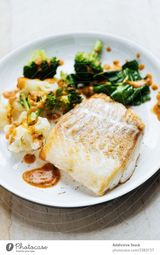 Fish with vegetables and sauce on plate fish broccoli green food fresh gourmet delicious tasty cuisine dish healthy ingredient portion culinary serve appetizing